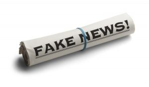 69458633 - rolled up newspaper with headline of fake news isolated on white background.